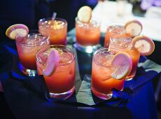 Tray of tequila sunrise cocktails being served at an event