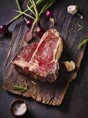 Rohes Dry Aged T-Bone-Steak auf Holzbrett