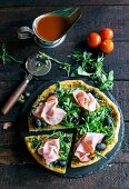 Served pizza topped with ham and rocket