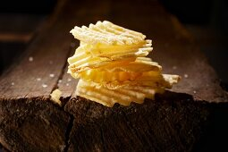 A stack of crinkle cut potato crisps on a wooden table