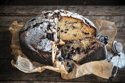 Homemade blueberry cake, sliced, on a wooden background