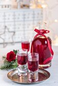 Homemade blackberry liqueur in glasses and a bottle for Christmas