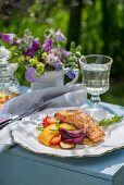 Salmon with a honey and lemon glaze, with summer vegetables on a table outdoors