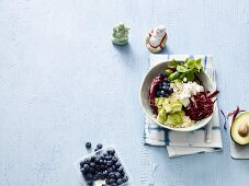 A Buddha bowl with couscous, avocado, blueberries and soft goat's cheese