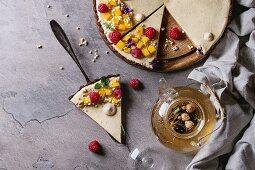 Schokoladen-Käsekuchen dekoriert mit Mango, Himbeeren, Puffreis und Essblüten
