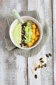 A green smoothie bowl with pumpkin seeds, grapes, mango and sesame seeds