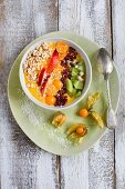 A yellow smoothie bowl with fruits, barberries and buckwheat pops