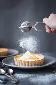 Dusting a lemon tart with icing sugar