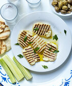 Sliced grilled halloumi with ouzo, olives, bread and gherkins (Cyprus)