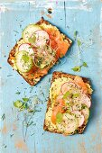Wholemeal bread with avocado and cream cheese spread, smoked salmon and sprouts