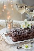 A festive chocolate log decorated with white flowers on a silver serving platter