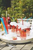 Drinks in glasses with paper lids and straws on a garden table