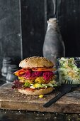 A spelt burger bun with coleslaw, beetroot, and sweet potato