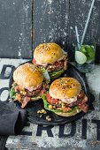 Burgers with beef, cocktail mayo, bacon, and pineapple salsa