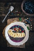 Berry smoothie bowl with bananas, chia, pumpkin seeds and oat flakes
