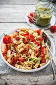 Fusilli salad with fresh cherry tomatoes, roasted peppers and pesto
