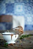 Schneebesen mit Resten von Schokoladencreme auf Vintage-Schüssel