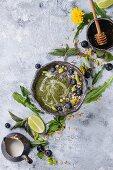 Grüne Smoothie-Bowl mit Löwenzahn und Brennesseln serviert mit Chia, Haferflocken und Heidelbeeren