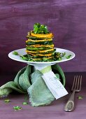 A zucchini and sweet potato tower with a card