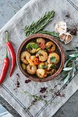 Garlic prawns with tomatoes and fresh herbs in a rustic serving dish