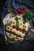 Vegan focaccia with tomato, olives and basil