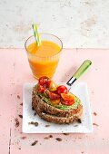 Carrot and fruit juice, and toasted bread with avocado cream and cherry tomatoes