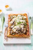 A savoury puff pastry tart with leeks, wild mushrooms, bacon and quails eggs