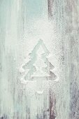 A fir tree drawn in powdered sugar on a white wooden background