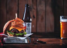 A burger with hand-cut rumpsteak, bacon, barbecue sauce, cheese, and onion rings