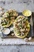 Naan pizzas topped with chicken and vegetables, with peanut and coconut sauce