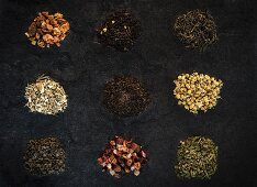 Seven Assorted Loose Teas in Bowls and Canisters