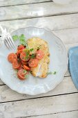 A fried redfish fillet with tomato salad