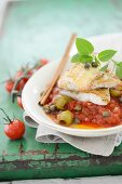 Fish fillets on tomatoes with green olives