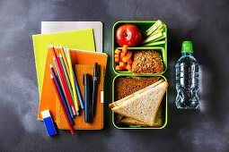 Take out food Lunch box with Sandwiches and vegetables, bottle of water and school supplies