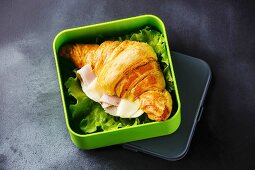 Take out food Croissant sandwich with cheese, ham and lettuce in Lunch box on blackboard background