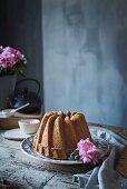 Bananen-Kranzkuchen auf rustikalem Holztisch vor grauem Hintergrun
