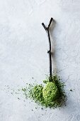 Matcha tea powder on a spoon against a gray background (top view)