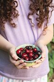 A young girl holding a bowl of fresh cherries