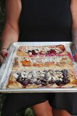 Three puff pastry pastries with cherries, apricots, and plums on a baking sheet