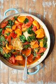 Chicken thights braised with sweet potatoes, spinach and tomatoes