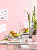 Gedeckter Tisch mit Salat, Wein und Frühlingsblumen zu Ostern