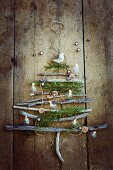 Rustic Christmas tree made from twigs on wooden wall