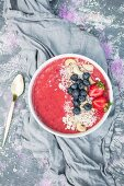 A strawberry smoothie bowl with blueberries, cashew and cereal flakes