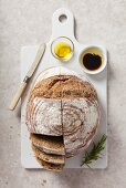 A loaf of sliced sourdough bread served on a white ceramic chopping board with olive oil and balsamic vinegar