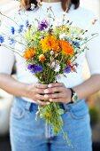 Hands holding a bouquet of wild summer flowers