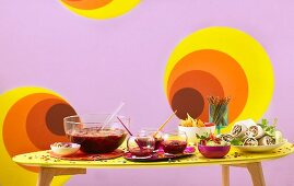 A table laid with wine punch, guacamole and wraps for a retro party
