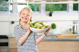 A girl holding a bowl of popcorn salad