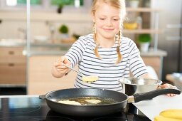 A girl frying banana pancakes in a pan