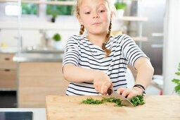 A girl chopping fresh parsley