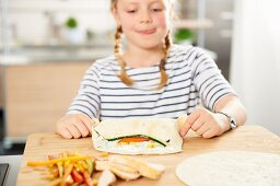 A girl making wraps with chicken breast, zucchini and corn